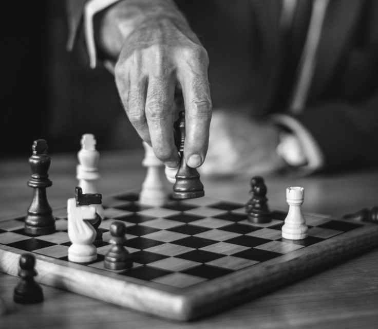 grayscale photo of person holding chess piece